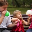 Family blow balloons sitting on bench in park — Stock Video #27545891