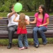 Family play game with balloons sitting on bench in park — Stock Video