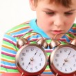 Boy holding pair of ringing alarm clocks near his ear — Stock Video