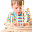 Boy with interest constructing toy model of ship — Stock Video #27546771