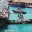 Two towing boats rotates tanker in seport — Stock Video #27546997