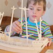 Boy with interest constructing toy model of ship — Stock Video #27547135