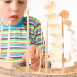Boy with interest constructing toy model of ship — Stock Video