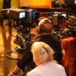 Stock Video: Back view of cameramans and spectators in big TV studio during filming