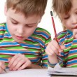 Stock video: Girl and boy with a chocolate-smeared mouth draw pictures in notebooks
