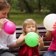 Family blow balloons sitting on bench in park — Stock Video