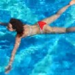 Woman in swimsuit lying on water surface of swimming pool — Stock Video