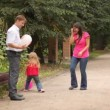 Parents and daughter play some game with balloons — Stock Video #27548907