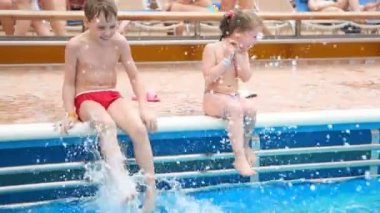 Boy and girl sits near outdoor swimming pool — Stock Video