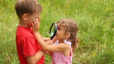 Sister is looking at her brother through the lens — Vídeo stock