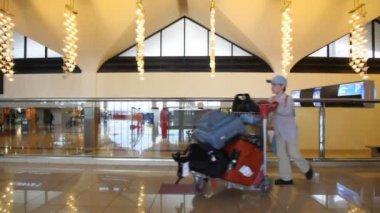 Junge mit gepäckwagen spaziergänge im flughafen — Stockvideo