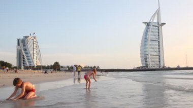 Kids playing on beach near Burj Al Arab five-star hotel during sunset — Stock Video