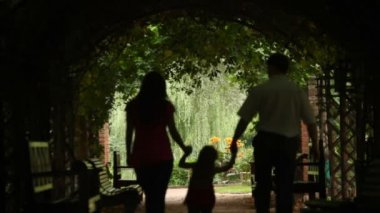 Silhouettes of parents with kid who walks in plant tunnel — 图库视频影像