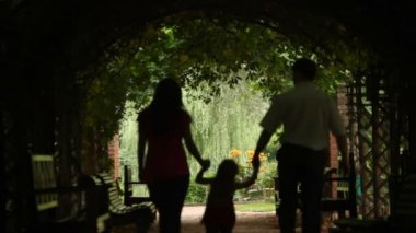 Silhouettes of parents with kid who walks in plant tunnel — Stock Video