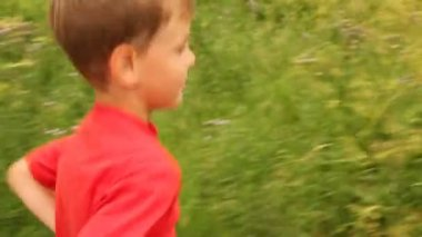 Boy is running merrily across a field — Stock Video