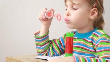 Uma menina sentada na mesa, soprando bolhas de sabão — Vídeo stock