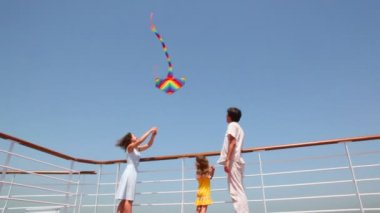 Bottom view on family flying kite on deck of ship — Stock Video