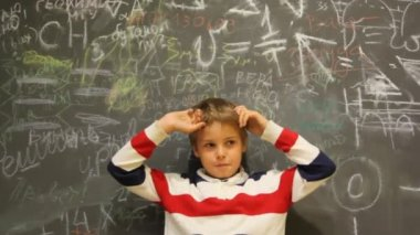 Puzzled boy stands against chalkboard covered with writing — Stock Video