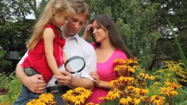 Girl and her parents discovering flower with magnifying glass — Vidéo