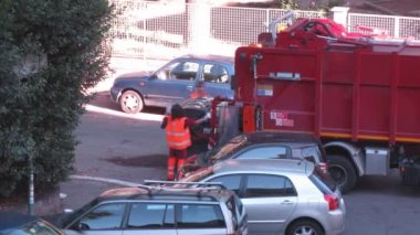Two workers lift trash bin into garbage truck at street — Stock Video