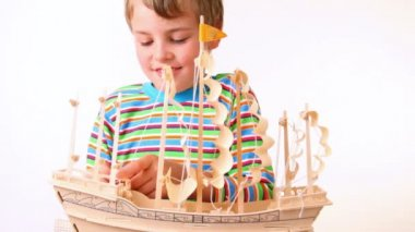 Boy sets up sails of toy model of ship — Stock Video