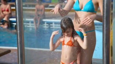 Woman and girl taking a shower near water pool — Stock Video