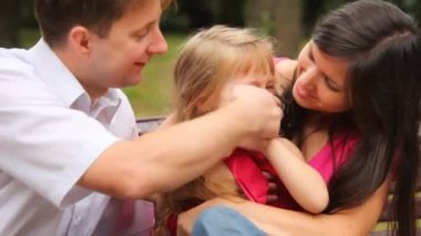 Couple and their daughter play game with fingers in park — Stok video