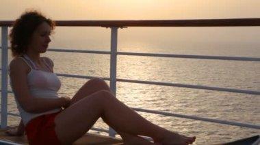 женщина, лежа на шезлонге на палубе круизный лайнер — Стоковое видео