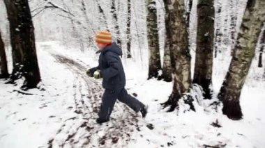 Ragazzo con palla di neve corre rotondo nella foresta di neve — Video Stock