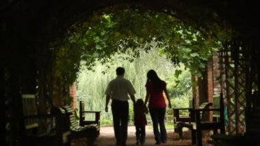 Silhouettes of parents with kid who walks in plant tunnel — Vídeo de Stock