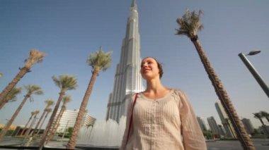 Mujer delante de fuentes cerca de burj dubai lake hotel en dubai, emiratos árabes unidos — Vídeo de Stock