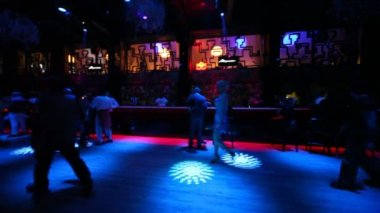 Some sit and relax at bar in dark nightclub with nice illumination — 图库视频影像