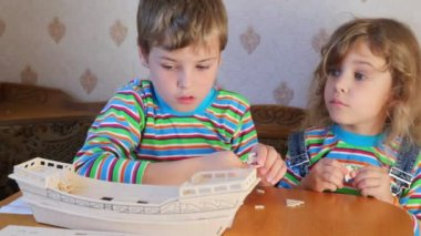 Boy and girl together constructing toy model of ship — Stock Video