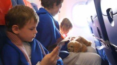 Rodina zabalená v pokrývce sedí na palubě letadla — Stock video