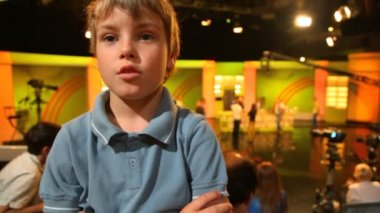 Boy standing in big TV studio with spectators — Stockvideo