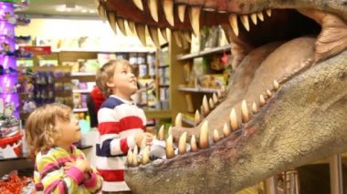 Kids looks at mouth of toy dinosaur — Stock Video