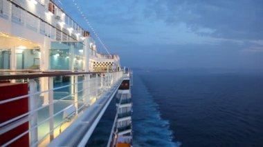 Boy walks on cruise ship in night sea — Stock Video