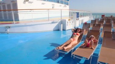 Mother and daughter in bikini lying on deckchairs — Stock Video