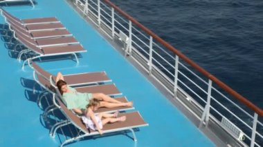 Woman and girl lying on deck chairs — Stock Video