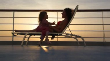 Silhouettes of mother and daughter on deckchair of ship — Stock Video