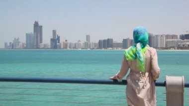 Woman stand on shore and looks at skyscrapers in Abu Dhabi, UAE — Stock Video