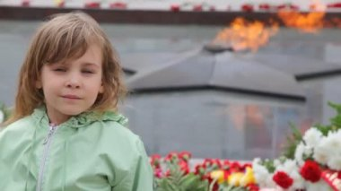 Girl standing against eternal fire on monument to unknown soldier — Stock Video