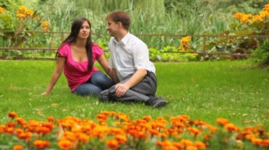 Couple sitting in park amid flowers — Vídeo de Stock