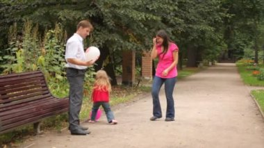 Parents and daughter play some game with balloons — Vídeo de Stock