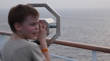 Boy looks at sea through binocular on deck of cruiser — Vídeo Stock
