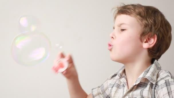 Chico sentado y soplando enorme soap bubble — Vídeo de stock