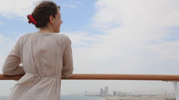 Mujer se encuentra en la cubierta y se ve en la ciudad — Vídeo de stock