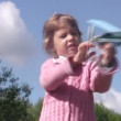 Little girl plays with toy plane and launch it in park. Sunny summer day. — Stock Video