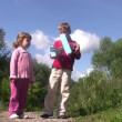 Stock Video: Little girl and boy stand in park, boy launch toy plane. Sunny summer day.