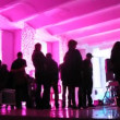 People walk inside pink lit room while filming video clip — Stock Video